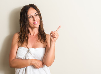Beautiful middle age woman, wet hair wearing a towel very happy pointing with hand and finger to the side