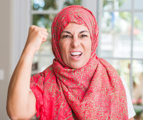 Middle aged muslim woman wearing hijab annoyed and frustrated shouting with anger, crazy and yelling with raised hand, anger concept