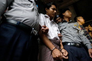 Detained Reuters journalist Kyaw Soe Oo is escorted by police officers as he leaves the Insein court in Yangon