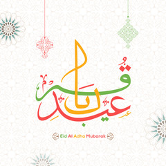 Colorful calligraphy of Eid Al Adha text on Islamic seamless pattern background decorated with hanging ornamental elements for celebration of Festival of Sacrifice.