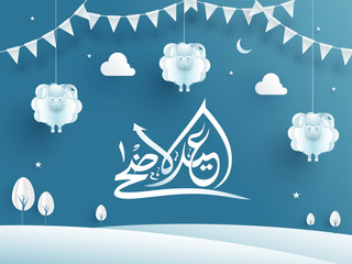 White calligraphy of Eid Al Adha Mubarak text on shiny blue background decorated with paper cut out of landscape, hanging sheep, cloud and bunting flag.