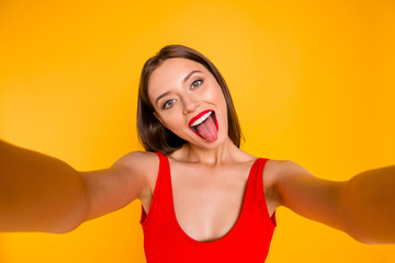Close up portrait of emotional girl taking selfie shot, grimacing makes memories at holiday and for her blog isolated on bright yellow background