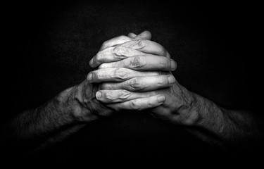 Man's Hands with crossed fingers. This is a classical gesture of a person praying God in the christian religions.