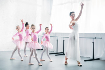young teacher practicing ballet with adorable kids in pink tutu skirts
