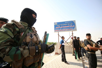 Iraqi security forces are seen during a protest at the main entrance to the giant Zubair oilfield near Basra