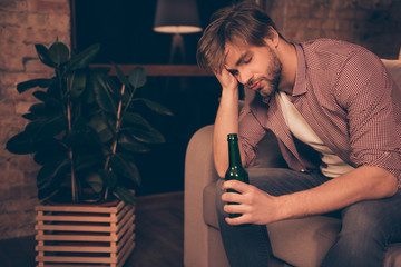 Portrait of unlucky, upset, tired, attractive, frustrated man holding bottle of beer in hand touching his head with arm having close eyes, bad luck, alcohol addiction, relationship problems