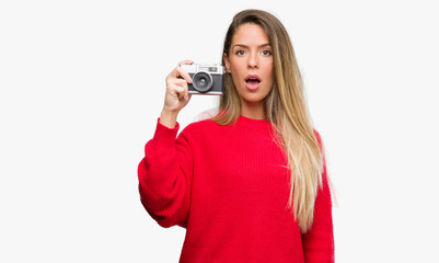 Beautiful young woman holding vintage camera scared in shock with a surprise face, afraid and excited with fear expression
