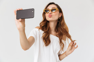 Image of stylish young woman 20s wearing sunglasses and jewelry taking selfie on mobile phone with kissing at camera, isolated over white background