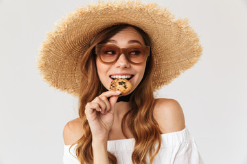 Image closeup of cheerful woman 20s wearing big straw hat and sunglasses eating biscuits, isolated over white background