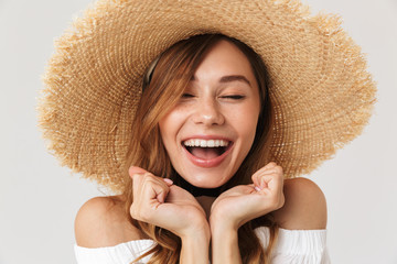 Portrait closeup of cheerful pretty woman 20s wearing big straw hat laughing with closed eyes, isolated over white background