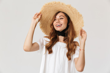 Portrait of modern cute woman 20s wearing big straw hat looking aside with happy smile, isolated over white background