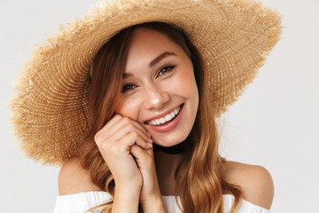 Photo of attractive woman 20s wearing big straw hat looking at camera with happy smile, isolated over white background