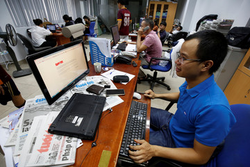 A journalist shows the banned online edition of Tuoi Tre newspaper at the newspaper's office in Hanoi