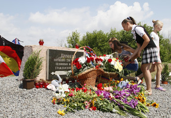 People gather near a monument for the victims of the Malaysia Airlines flight MH17 plane crash to mark the fourth anniversary of the accident in Donetsk Region