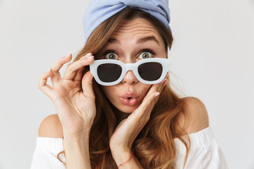 Photo closeup of surprised stylish woman 20s looking at camera from under sunglasses, isolated over white background