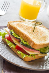 Sandwich with cheese, ham and fresh vegetables on a plate. Fresh juice and a Cup of coffee. The concept of Breakfast.