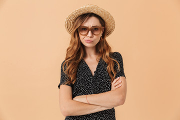 Portrait of disappointed woman 20s wearing straw hat and sunglasses standing with arms crossed, isolated over beige background