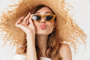 Portrait of stylish fashionable woman 20s wearing big straw hat and sunglasses giving kiss at camera, isolated over white background