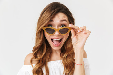 Portrait closeup of excited amusing woman 20s looking at camera from under sunglasses, isolated over white background