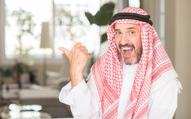 Middle age arabian man at home pointing with hand and finger up with happy face smiling