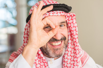 Middle age arabian man at home with happy face smiling doing ok sign with hand on eye looking through fingers