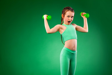 Kid girl doing fitness exercises on green background