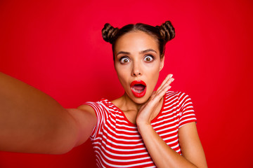 OOPS! Self portrait of cute, trendy and shocked woman with bun hairdo wide open eyes mouth shooting selfie on front camera isolated on red background