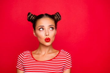 Attractive young girl with nice make up wearing striped tshirt puffed up her lips and looked up isolated on bright red background with copy space