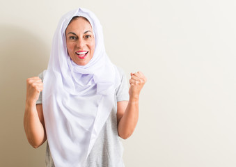 Middle age arabian woman wearing white hijab screaming proud and celebrating victory and success very excited, cheering emotion