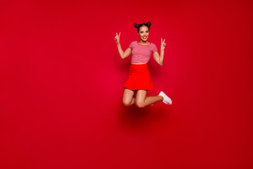 Full-length full-size view of jumping laughing and pretty woman dressed in colourful bright clothes shows a v-sign isolated on red background. Joy fun concept