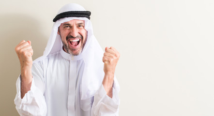 Senior arabic man screaming proud and celebrating victory and success very excited, cheering emotion