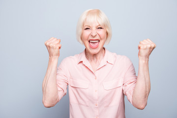 Old adult blonde glad excited cheerful lady smiling, laughing, screaming, raising hands, opened mouth, over grey background, isolated