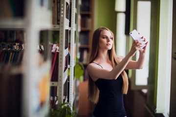 Image young smiling woman student sitting in library make selfie with peace gesture by mobile phone. Looking aside.