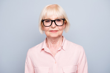 Portrait of old adult blonde glad cheerful caucasian lady smiling, wearing eye glasses over grey background, isolated