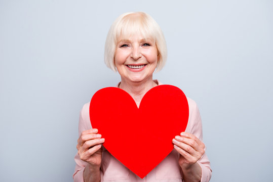 Portrait of old adult blonde caucasian glad lady holding hands big red paper heart shape, smiling over grey background, isolated