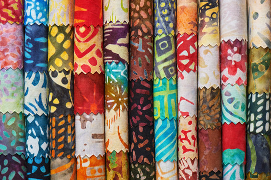 Stack of colorful quilting batik fabrics as a vibrant background image