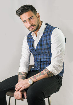Trendy young man in studio shot wearing elegant vest and white shirt, looking at camera