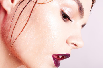 Close up fashion face view with wet skin and bright make up. Side view with drops on cheek. Closed eyes.
