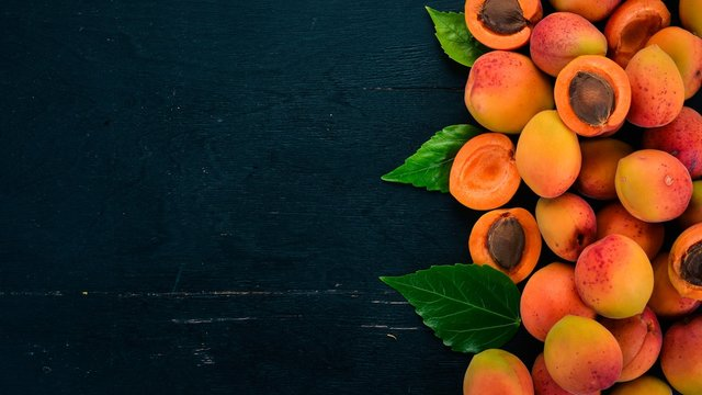 Fresh apricots with leaves On a black wooden background. Top view. Free space for your text.