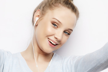 Blond girl in headphones listening music taking photo makes self portrait on smartphone wearing a casual clothes