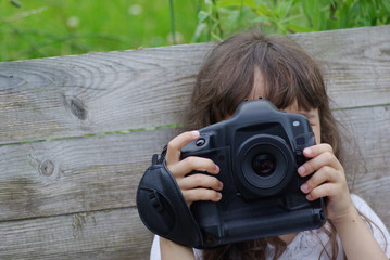 Little girl takes pictures on a big camera