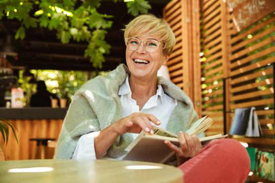 Happy mature woman wrapped in blanket reading a book