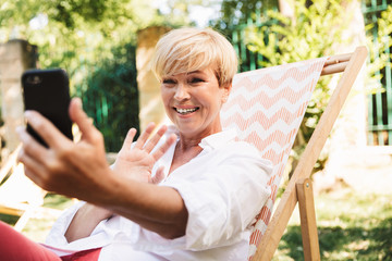 Happy mature woman having a video chat