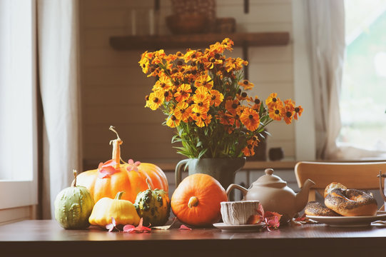 cozy autumn breakfast on table in country house. Hot tea, pumpkins, bagels and flowers.