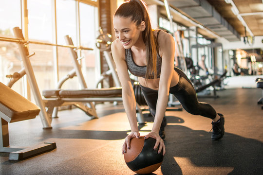 Beautiful sporty woman doing push up on ball in the gym