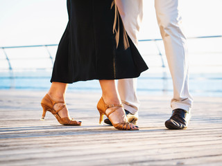 Young attractive couple dancing latin bachata near sea or ocean. Sunlight background. Summer time, romantic scene. Legs of professional dancers.