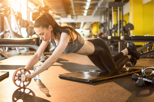 Attractive slim sportswoman workout with abdominal roller in gym