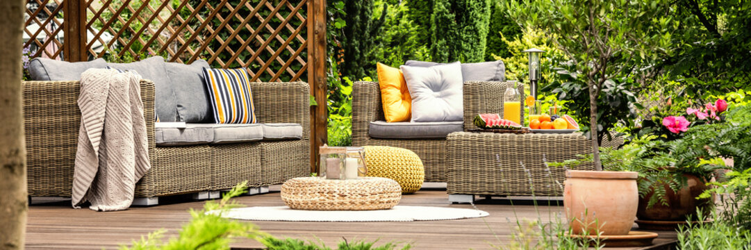 A spa hotel garden with cozy, wicker garden furniture and cozy, colorful pillows on a beautiful wooden terrace among outdoor greenery