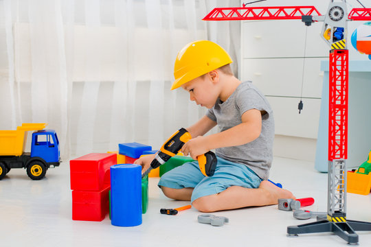 Small child 4 years old, playing with a large number of colorful plastic toys in the room, the construction of various facilities and trucks