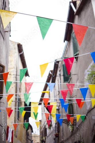 Multicolored festive bunting on narrow old street of a
